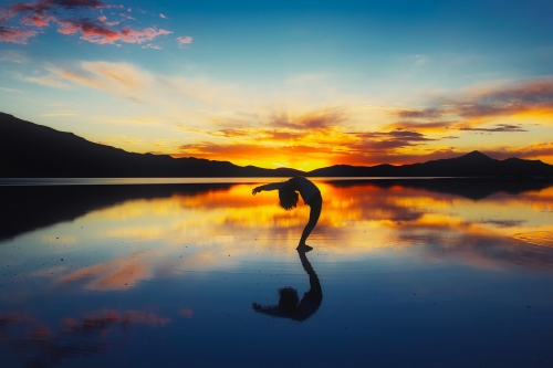 A picture of the sunset and a person doing yoga