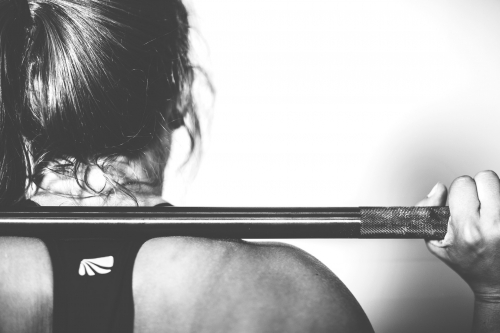 Exercise Therapy Girl with a barbell across shoulders.